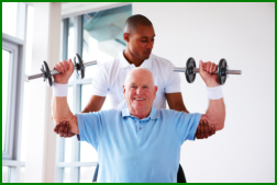 gymn instructor helping elderly in exercise